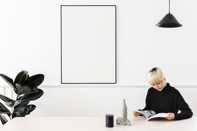 Femme asiatique aux cheveux blonds lisant un magazine avec un cadre vierge sur un mur
