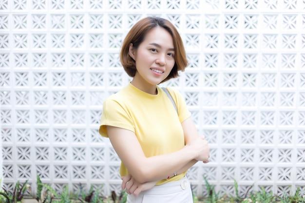 Une femme asiatique aux cheveux courts dorés porte un t-shirt à manches courtes de couleur jaune et un pantalon crème