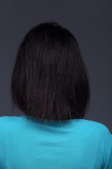 Femme asiatique avant d'appliquer le maquillage chemise bleue de style cheveux noirs. pas de retouche, visage frais avec acné, peau agréable et lisse. studio éclairage fond gris, vue arrière arrière