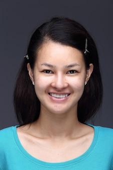 Femme asiatique avant d'appliquer le maquillage chemise bleue de style cheveux noirs. pas de retouche, visage frais avec acné, peau agréable et lisse. studio éclairage fond gris