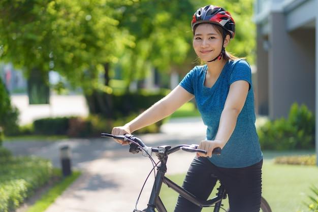 Femme asiatique ayant l'air heureuse en faisant du vélo dans son quartier pour la santé et le bien-être quotidiens, à la fois physiques et mentaux.