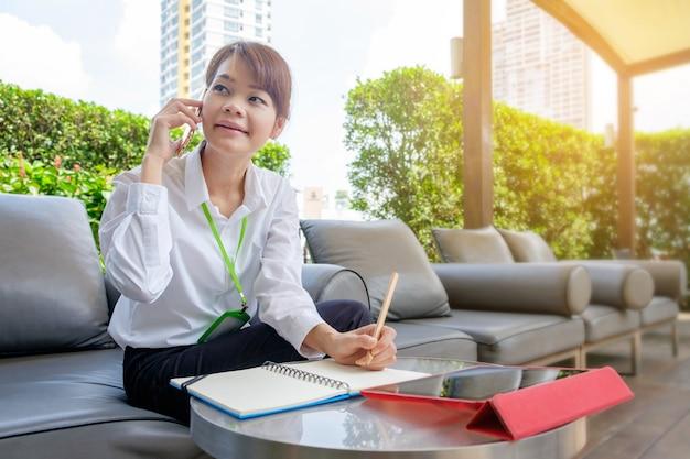 Femme asiatique ayant réussi des affaires, parlant sur son téléphone portable assis en plein air dans la ville.