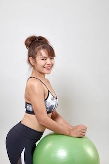 Femme asiatique avec ballon exercice