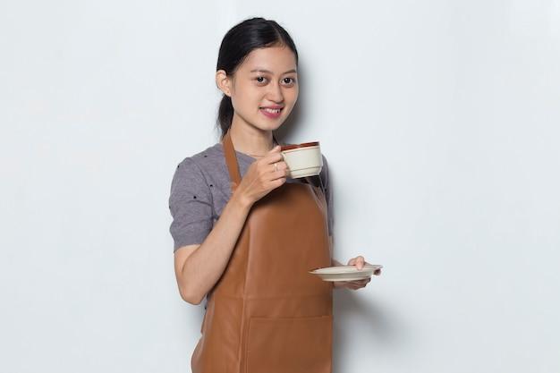 Une femme asiatique barista porte un tablier avec une tasse de café concept de service de café