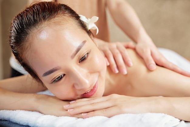 Femme asiatique bénéficiant d'un massage du dos