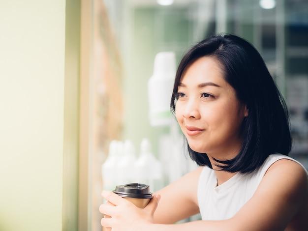 Femme asiatique boit du café chaud dans le café avec une lumière chaude.