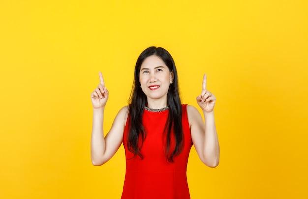 Femme asiatique en bonne santé adulte vêtue d'une belle robe sans manches pointant les doigts vers le haut sur fond jaune vif.