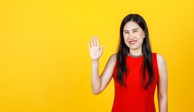 Une femme asiatique en bonne santé portant une belle robe sans manches, souriante sur un portrait isolé, fait un geste amical de salutation de la paume et exprime un signe joyeux de salut 5 message avec plaisir lors d'un événement luxueux