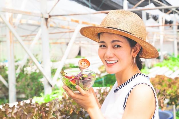 Femme asiatique en bonne santé tenant un bol de salade à la tomate en tranches. mode de vie heureux