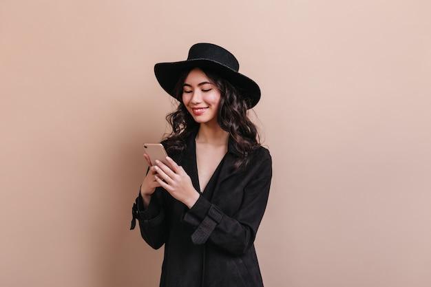 Femme asiatique bouclée tenant le smartphone. rire femme coréenne en manteau posant avec gadget.