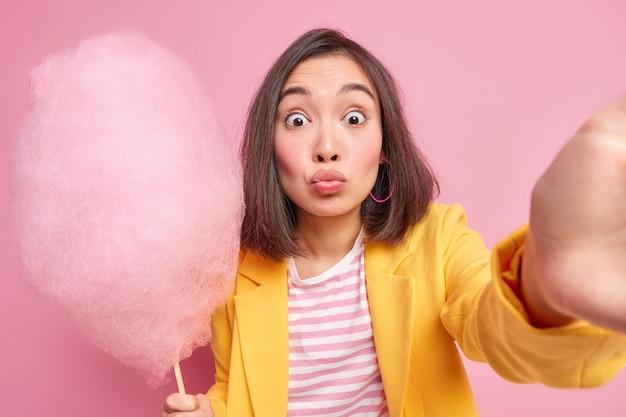 Une femme asiatique brune surprise aux cheveux noirs garde les lèvres arrondies, les yeux grands ouverts tiennent de délicieuses barbes à papa sur des poses de bâton pour faire un selfie habillé formellement isolé sur un mur rose