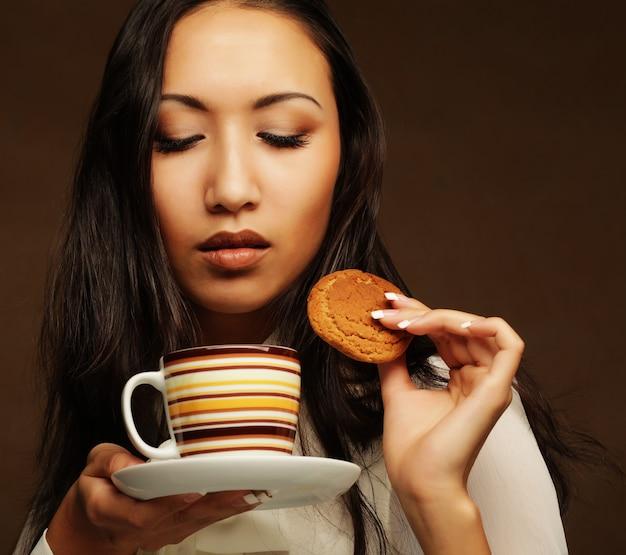 Femme asiatique avec café et biscuits.