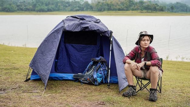 Femme asiatique camping au réservoir et asseoir dans une chaise
