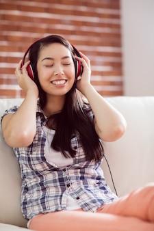Femme asiatique sur le canapé en écoutant de la musique