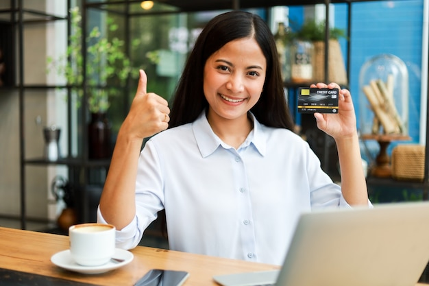 Femme asiatique avec carte de crédit, achats en ligne dans le café-restaurant