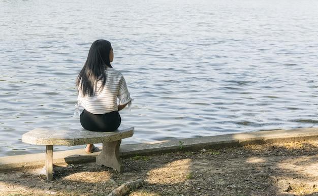 Femme asiatique sur une chaise assis seul sur le fond de la rivière, du pont et du lac.