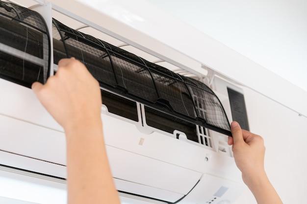 Femme asiatique changeant un filtre de climatiseur sale et poussiéreux dans la chambre. femme enlevant un filtre à air sale à l'intérieur du climatiseur.