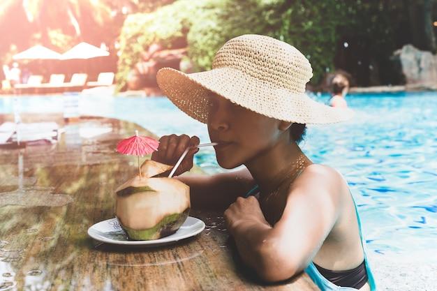 Femme asiatique avec un chapeau ayant une boisson de noix de coco dans la piscine