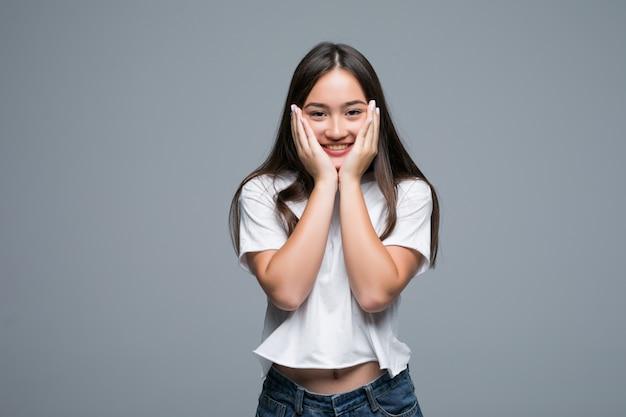Femme asiatique charmante posant et en détournant les yeux sur fond gris