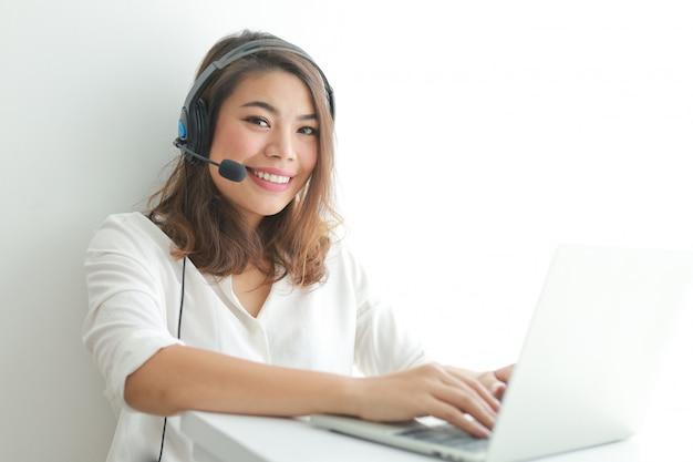Femme asiatique sur chemise blanche parler avec un casque et à l'aide d'un ordinateur portable, sourire et concept d'opérateur visage heureux