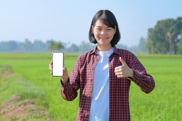 Une femme asiatique en chemise rayée rouge pose avec un smartphone montrant un écran vide et un pouce levé dans un champ.