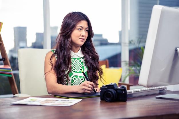 Femme asiatique ciblée à l'aide d'un tableau numérique et d'un ordinateur de bureau