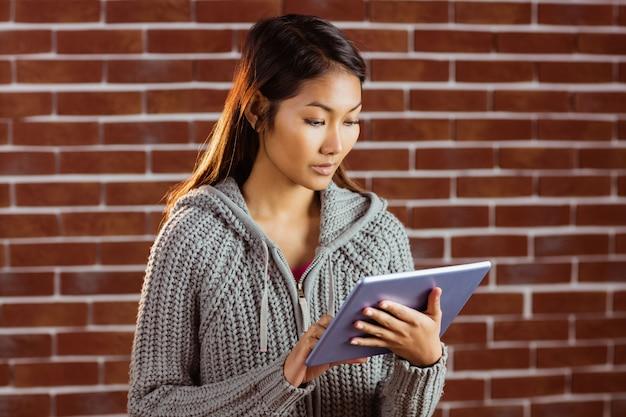 Femme asiatique ciblée à l'aide de tablette sur le mur de briques