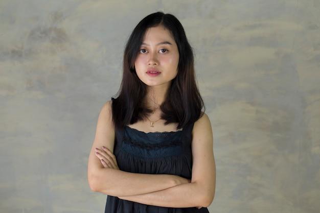 Femme asiatique confiante debout mains croisées