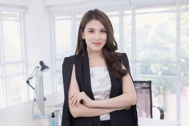 Une femme asiatique confiante est debout et croise les bras avec un visage souriant dans la salle de travail en arrière-plan