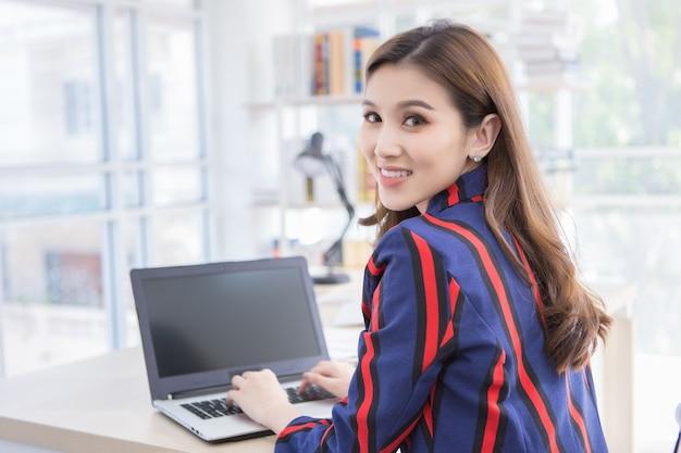 Une femme asiatique confiante pose sa main sur le clavier de l'ordinateur portable et se retourne