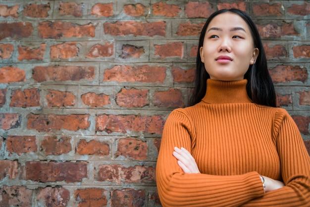 Femme asiatique, contre, mur brique