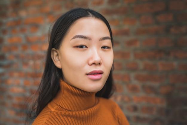 Femme asiatique contre le mur de briques.