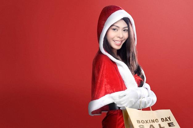 Femme asiatique en costume de santa tenant des sacs à provisions avec texte de vente de noël avec fond rouge