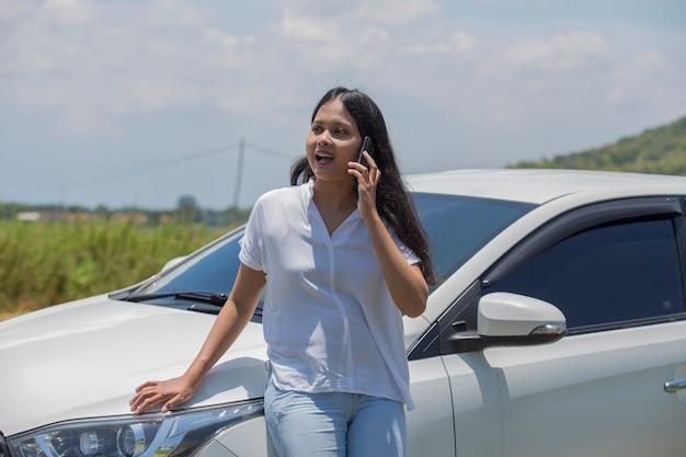 Femme asiatique à côté d'une voiture à l'aide d'un téléphone intelligent