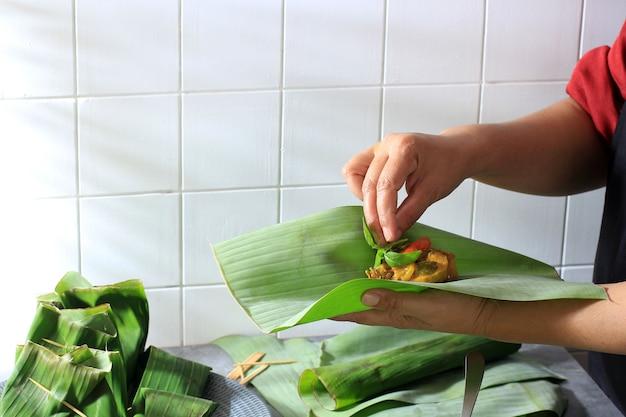 Femme asiatique cuisinant dans la cuisine, faisant étape par étape des pepes (plat d'accompagnement à la vapeur) d'indonésie. ajouter le basilic citronné avant d'envelopper pepes avec une feuille de bananier