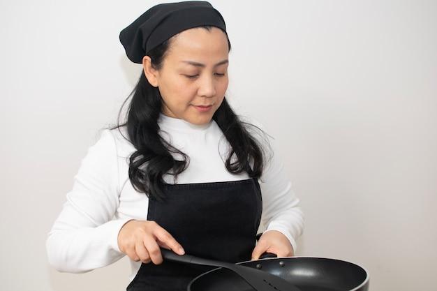 Femme asiatique en cuisine porte une casserole noire