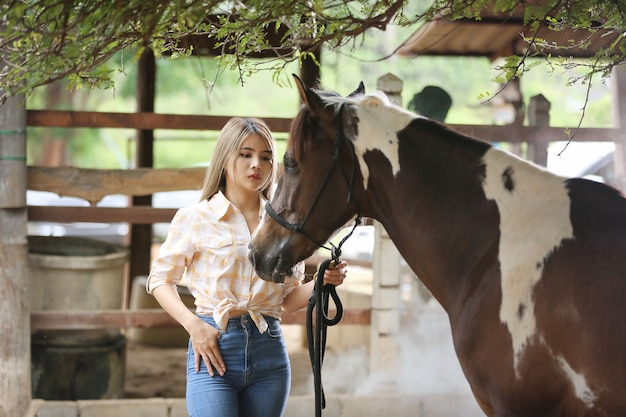 Femme asiatique dans un costume de cow-girl se tient avec un cheval dans une ferme d'élevage.