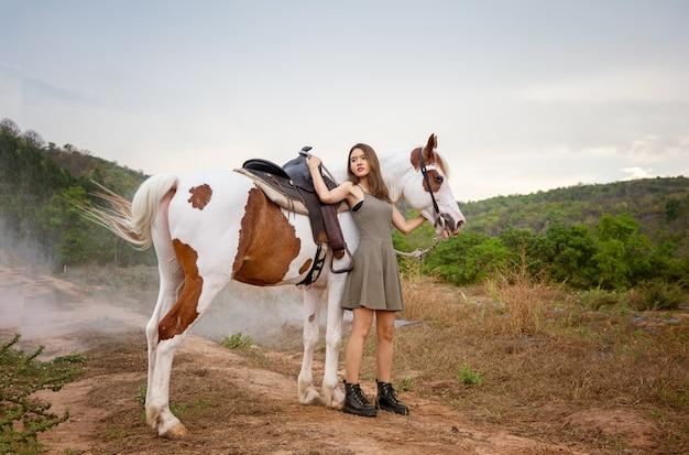 Femme asiatique dans un costume robe longue se tient avec un cheval dans une ferme d'élevage.