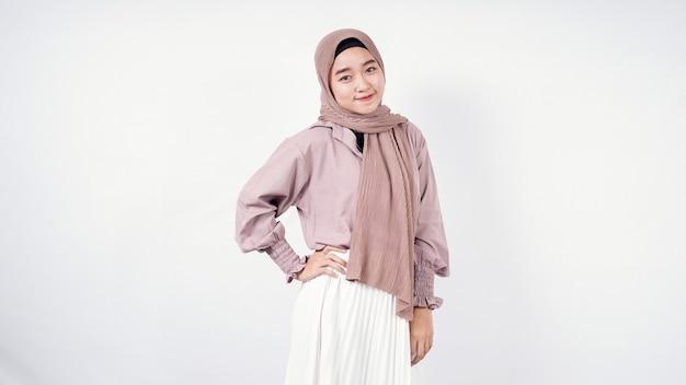 Femme asiatique, dans, hijab, poser, sourire, main droite, taille, isolé, blanc
