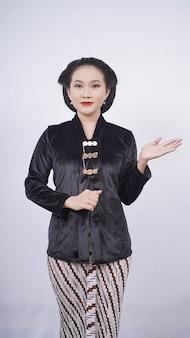 Femme asiatique, dans, kebaya, sourire, pointage, vide, côté, isolé, blanc, fond