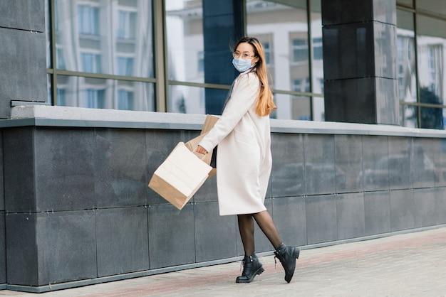 Femme asiatique dans un manteau, des lunettes et un masque médical se tient dans la rue, tenant un paquet dans ses mains.
