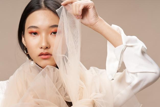 Femme asiatique dans le maquillage de vêtements élégants modèle de tissu transparent