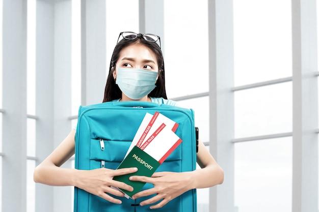 Femme asiatique dans le masque facial avec une valise tenant un billet et un passeport à l'hôpital. contrôle médical avant de voyager