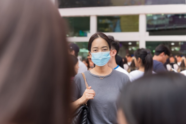 Femme asiatique, dans, masque médical, debout, dans, a, foule