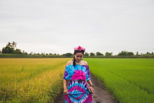 Femme asiatique dans une robe de couleur à motifs, elle se tient devant un champ de riz
