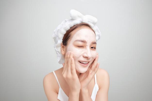 Femme asiatique dans une serviette blanche sur la tête avec un masque sur le visage