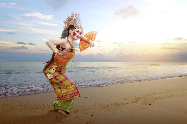 Femme asiatique danse danse traditionnelle balinaise (danse kembang girang) sur la plage