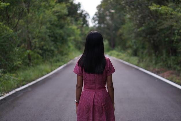 Femme asiatique debout au milieu de la route sur un fond de forêt verte
