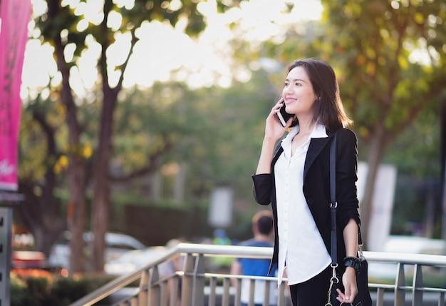 Femme asiatique debout en plein air. bonne femme parlant au téléphone.