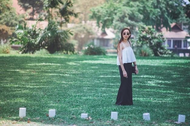 Femme asiatique debout et posant sur la pelouse verte